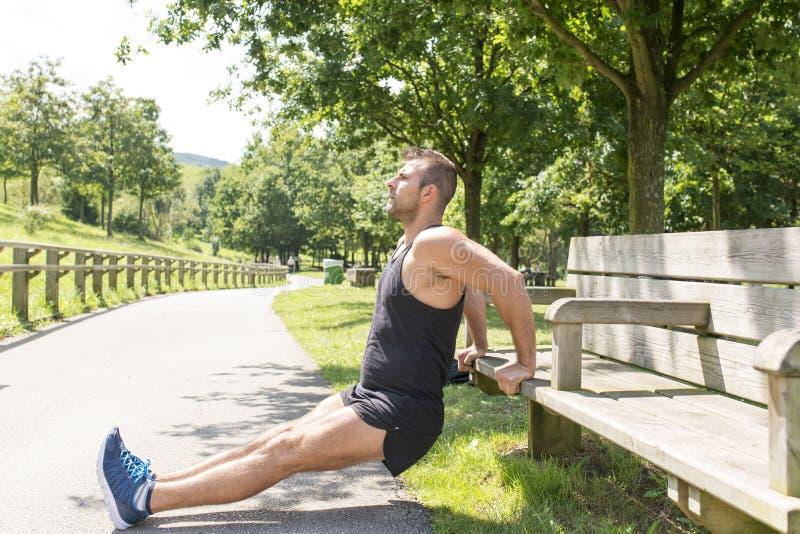 Sportowy mężczyzna szkolenie i ćwiczyć na ławce, plenerowej zdjęcie stock