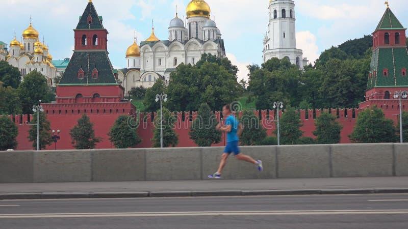 Sportowy młodego człowieka bieg przeciw Moskwa Kremlin fotografia royalty free