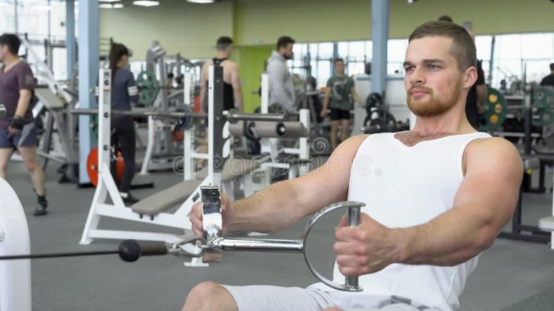 Sportowy młody człowiek ćwiczy na blokowym przyrządzie Portret silny sportowy mężczyzna przy gym szkoleniem fotografia royalty free