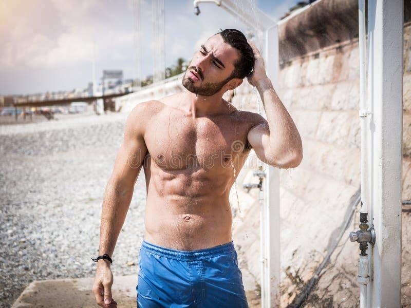 Sportowy młody człowiek bierze prysznic na plaży zdjęcia stock