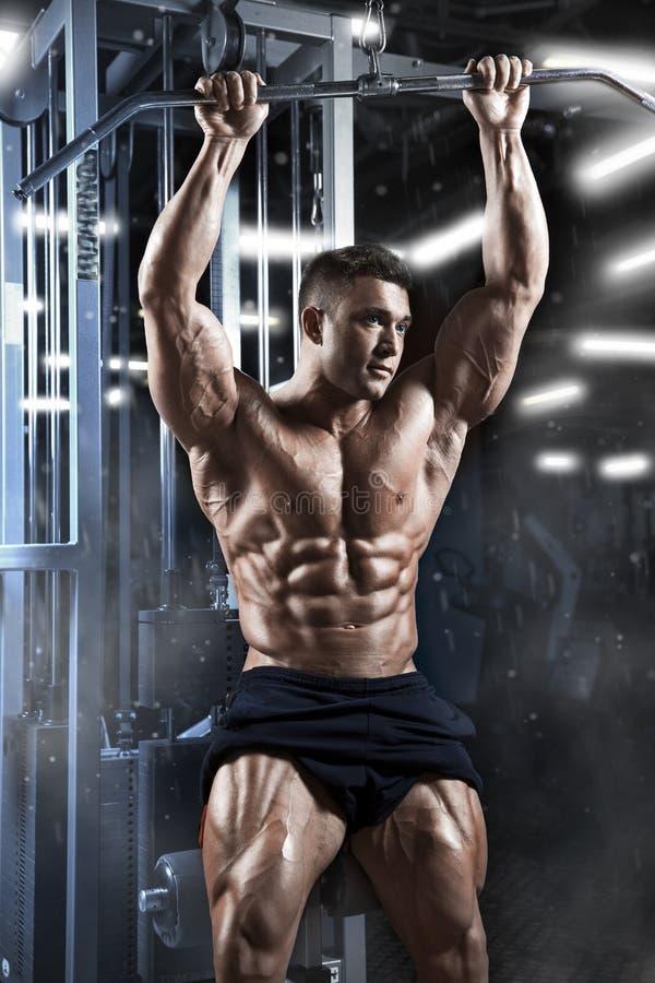 Sportowy mięśniowy facet przygotowywa robić ćwiczeniom z sportowym trenerem w gym zdjęcia stock