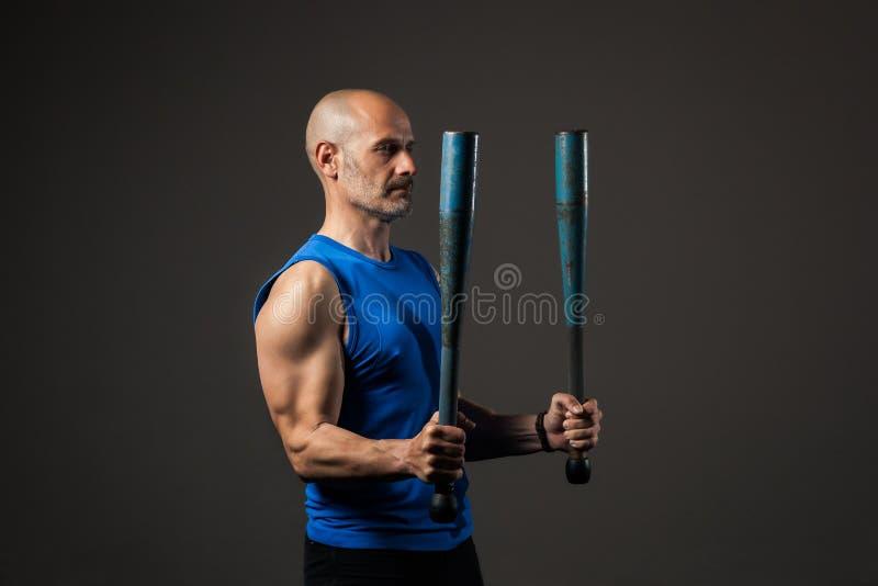 Sportowy, w średnim wieku mężczyzny szkolenie z clubbells, pracowniany tło fotografia royalty free