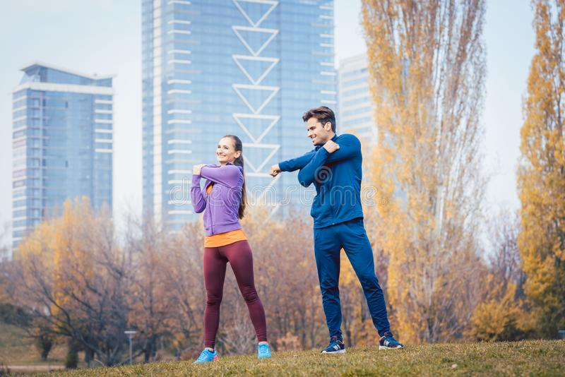 Sportpaar die opwarmingsoefening doen alvorens een looppas te beginnen royalty-vrije stock afbeeldingen