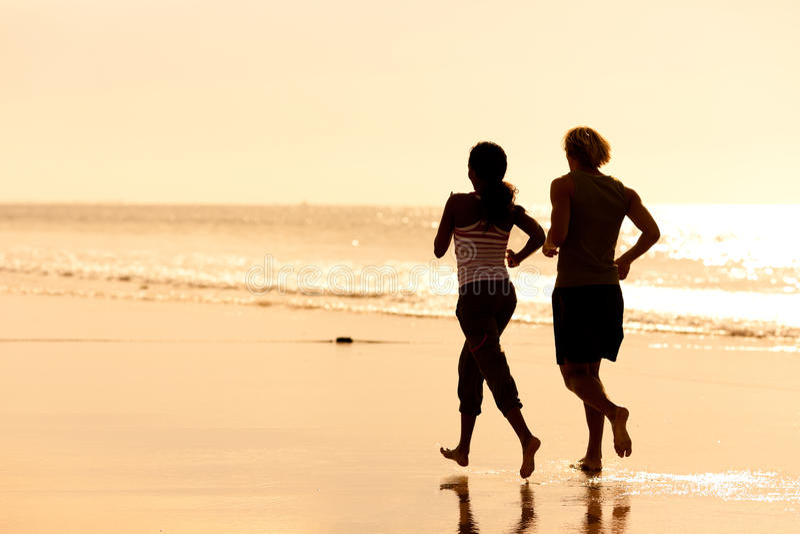Sportpaare, die auf dem Strand rütteln lizenzfreie stockfotografie