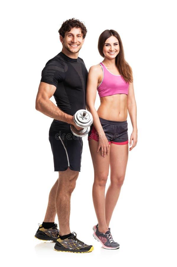 Sportpar - man och kvinna med hantlar på viten arkivfoton