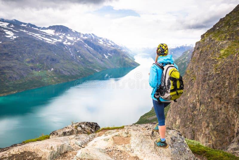 Sportpar som fotvandrar på Besseggen Fotvandrare tycker om den härliga sjön och bra väder i Norge royaltyfri fotografi