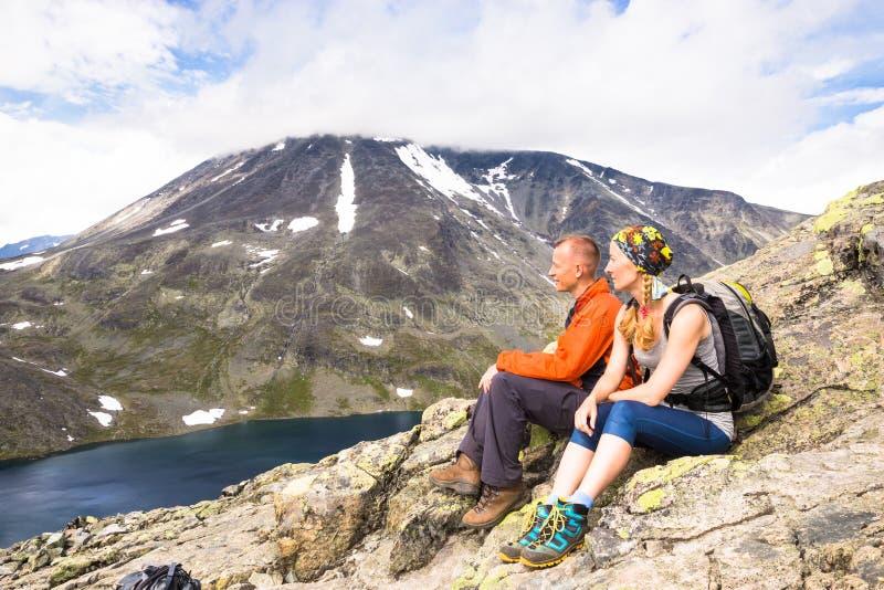 Sportpar som fotvandrar på Besseggen Fotvandrare tycker om den härliga sjön och bra väder i Norge arkivbilder