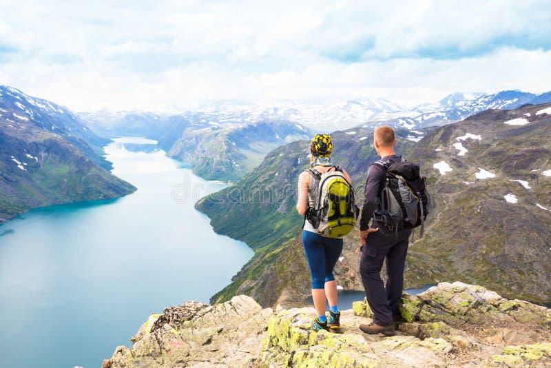 Sportpar som fotvandrar på Besseggen Fotvandrare tycker om den härliga sjön och bra väder i Norge royaltyfria bilder