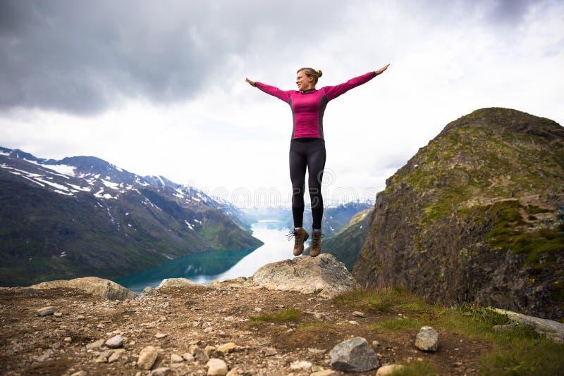 Sportpar som fotvandrar på Besseggen Fotvandrare tycker om den härliga sjön och bra väder i Norge royaltyfria foton