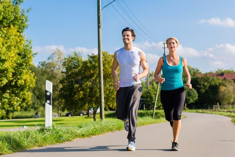 Sportparspring och jogga på den lantliga gatan royaltyfri fotografi