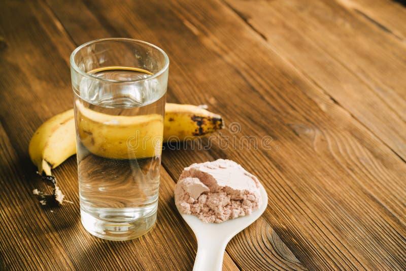 Sportprotein på skeden, en banan och ett exponeringsglas av vatten på wo royaltyfri foto