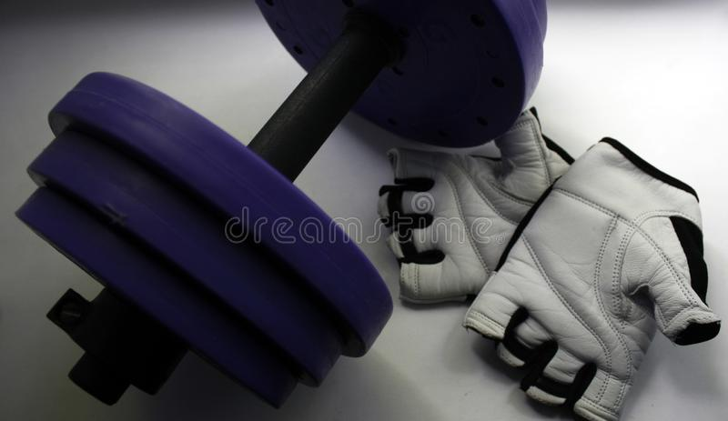 Sports accessories. Dumbbells, gloves, on a white background. Top view with copy space. Fitness, sport and healthy lifestyle stock images