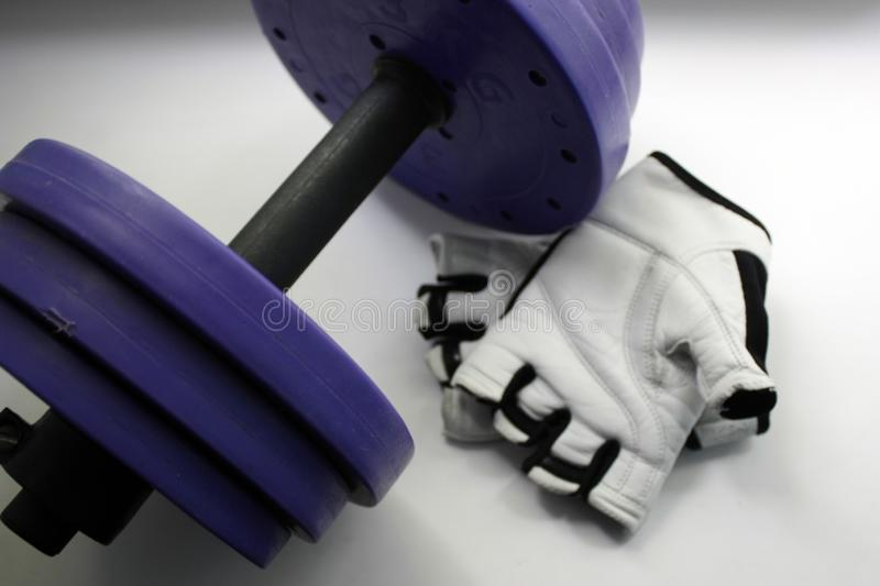 Sports accessories. Dumbbells, gloves, on a white background. Top view with copy space. Fitness, sport and healthy lifestyle stock photos