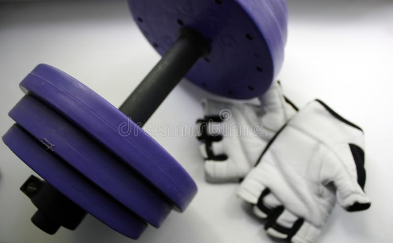 Sports accessories. Dumbbells, gloves, on a white background. Top view with copy space. Fitness, sport and healthy lifestyle stock image