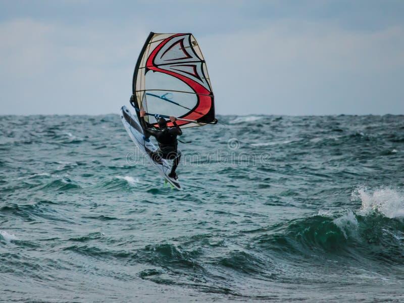 Sports aquatiques : La planche à voile saute de l'eau image libre de droits