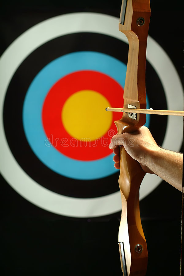 Sports archer preparing to fire stock photography