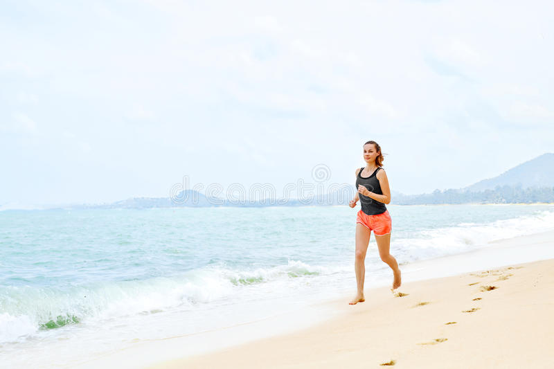 Sports. Athlete Jogging On Beach. Fitness, Exercising, Healthy L. Sports. Fit Female Athlete Jogger Running On Beach. Sporty Athletic Woman Jogging During stock photo
