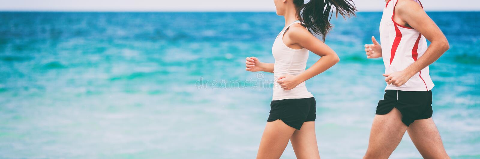 Sports athletes runners couple training together jogging on blue ocean background panoramic banner with copyspace. Two joggers royalty free stock images