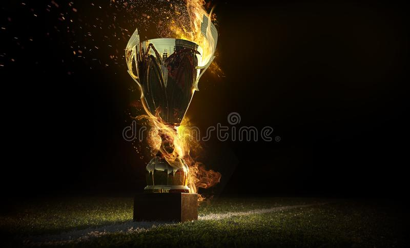Sports background. Burning trophy goblet. Winner in a competition. Fire and energy. Football field with golden goblet. royalty free stock image