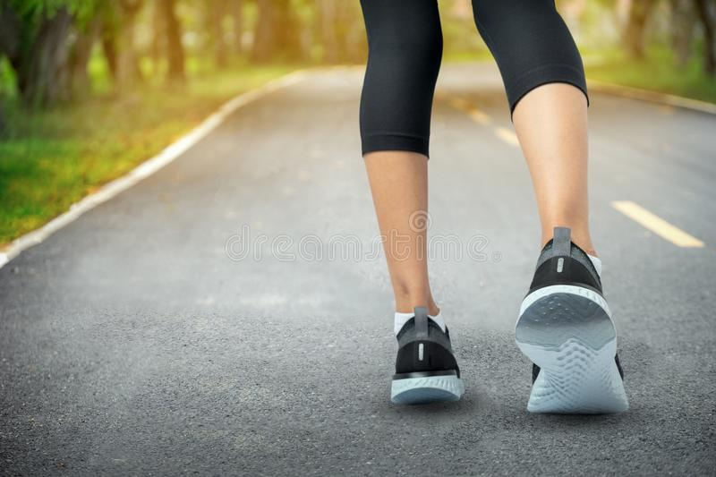 Sports background, Runner feet running on road closeup on shoe, Sport woman running on road at sunrise, Fitness and workout. Wellness concept stock photo
