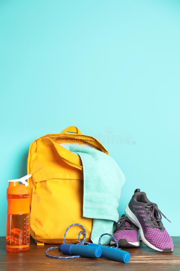 Sports bag and gym equipment on wooden floor color background. Sports bag and gym equipment on wooden floor against color background stock photo