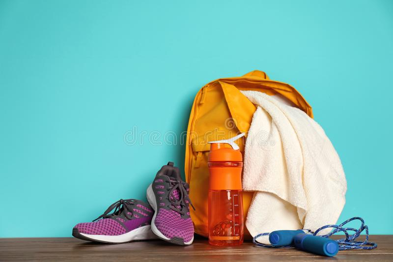 Sports bag and gym equipment on wooden floor. Against color background royalty free stock photo