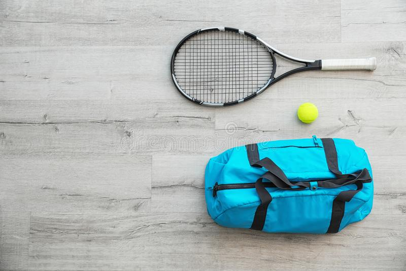 Sports bag, racket and ball on wooden floo. R, top view royalty free stock image
