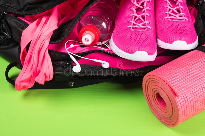 Sports bag with a set of sportswear, headphones and a bottle of water, from below the place for an inscription, on a green backgro royalty free stock photo