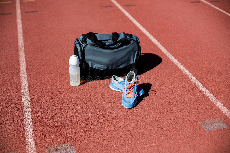 Sports bag, shoes and a water bottle kept on a running track. In stadium royalty free stock images