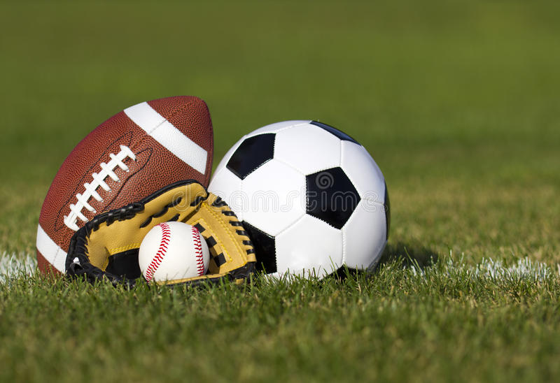 Sports balls on the field with yard line. Soccer ball, American football and Baseball in yellow glove on green grass. Outdoors royalty free stock photos
