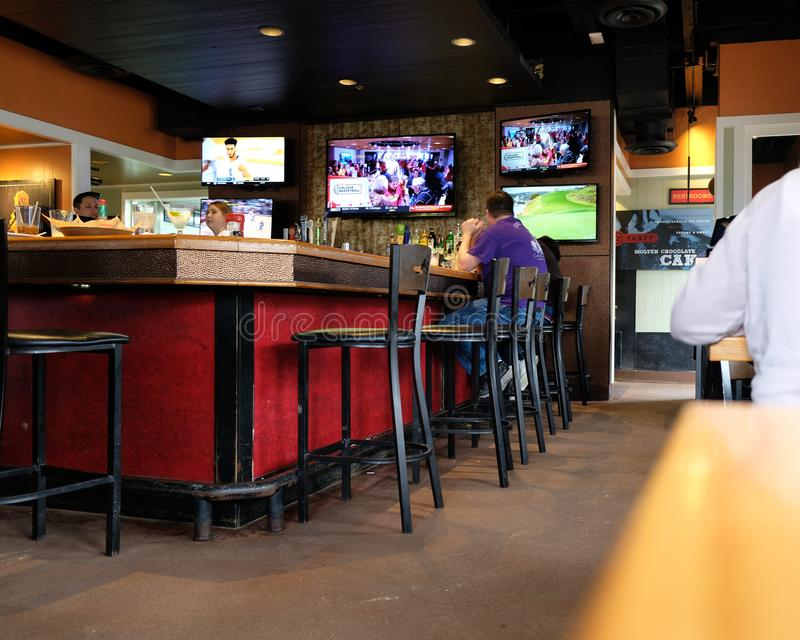 Sports bar or pub interior. Interior scene of a sports bar or pub with bar stools, televisions and patrons royalty free stock image