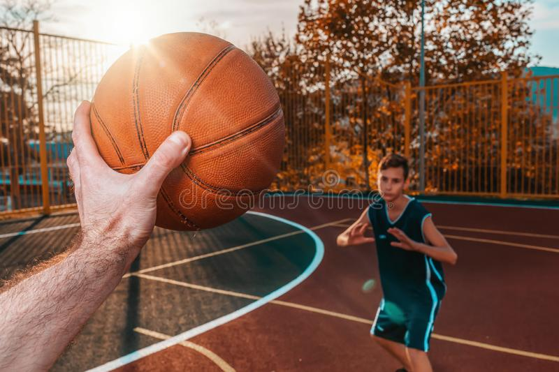 Sports and basketball. A man`s hand holds a basketball for submission. In the background, a teenager in a blur preparing to catch. A ball. Sunlight stock photography