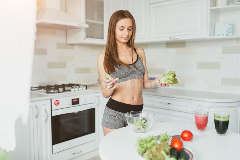 Sports beautiful young girl does salad after a hard workout fitness. She eats healthy food stock photography