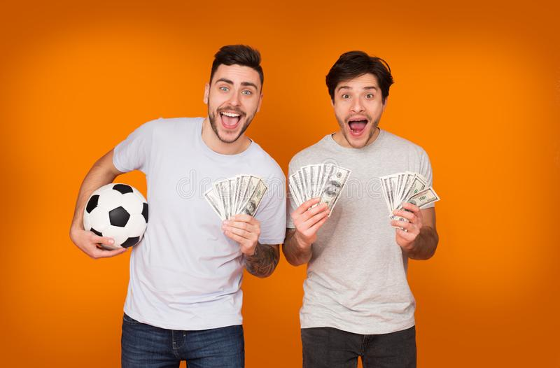 Sports Betting. Excited Men Enjoying Their Win. Holding Soccer Ball And Lots Of Money, Orange Background royalty free stock photo