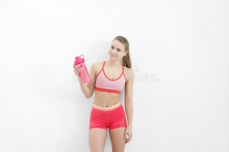 Sports blonde girl in red training clothes and with a white towel on her shoulders. He holds in his hand and drinks. Water from a bottle, in the studio on a stock photos