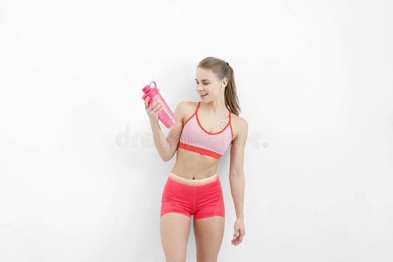 Sports blonde girl in red training clothes and with a white towel on her shoulders. He holds in his hand and drinks. Water from a bottle, in the studio on a stock image