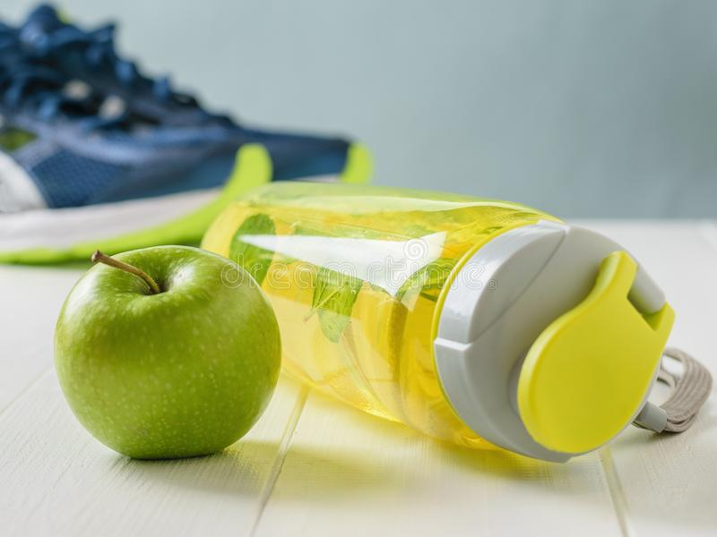 Sports bottle with a refreshing drink and a green Apple on the background of running shoes. stock photography