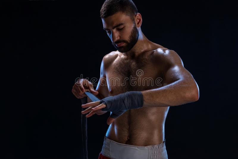 Sports boxer man pulls on the hand wrist wraps. Oriental male model isolated on black background. royalty free stock photography