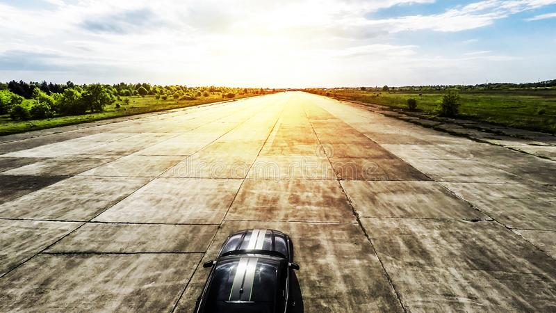 Black sports car on abandoned runway ready to race. Sports car ready to race stock images