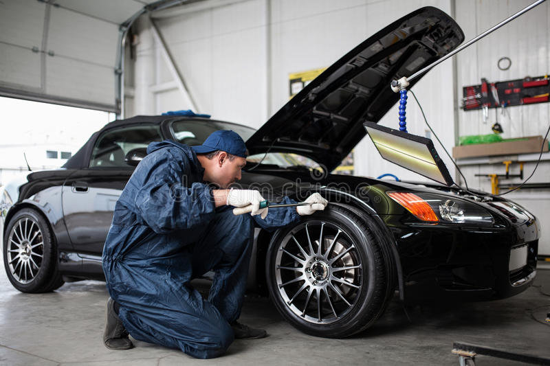 Sports car in a workshop. Sports car in a service workshop - fixing a dent stock photography