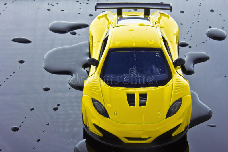 Sports car. Yellow sports car isolated over water drops background royalty free stock photo