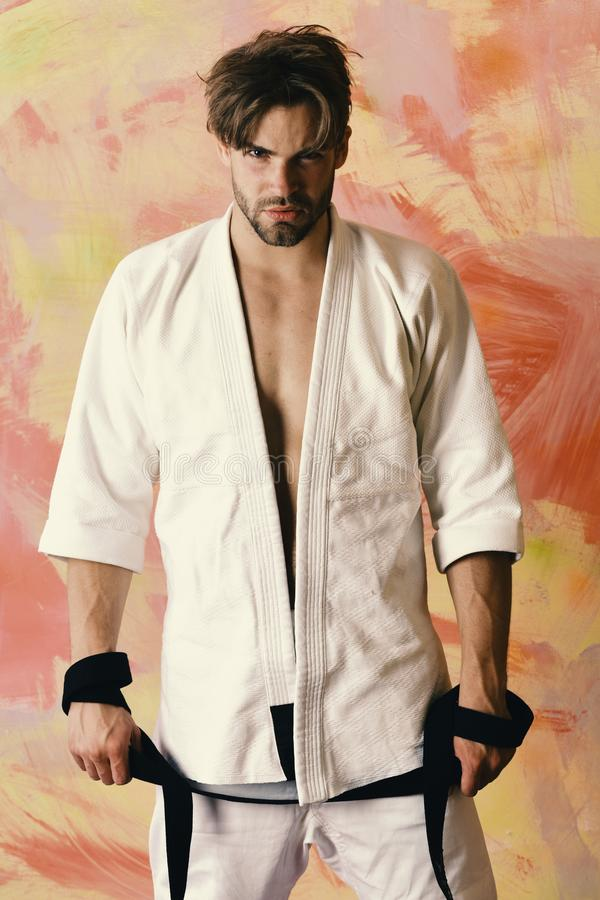 Sports and combat concept. Guy poses in white kimono holding black belt stock photo