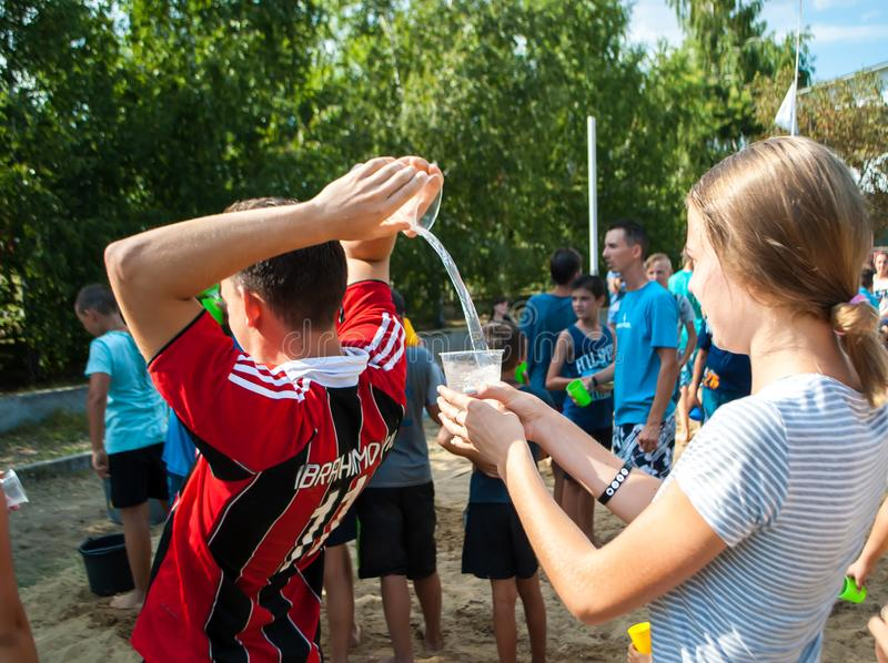 Sports competitions with water in the summer camp.The guy pours water behind his back from the cup to another cup stock image