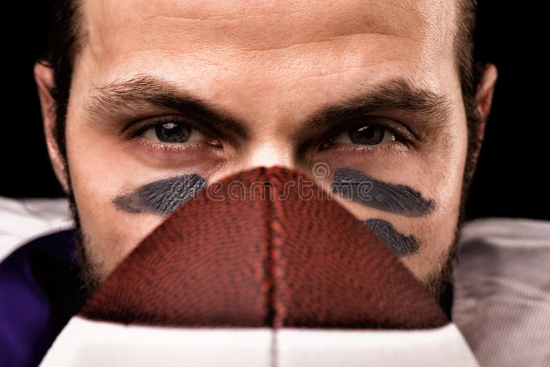 Sports concept. American football player on black with ball. Sports concept. close-up stock photography