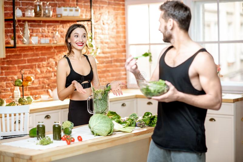 Sports couple eating healthy vegetarian food on the kitchen royalty free stock images