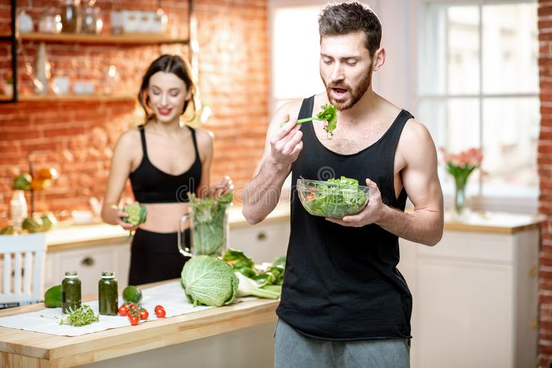 Sports couple eating healthy vegetarian food on the kitchen royalty free stock photos
