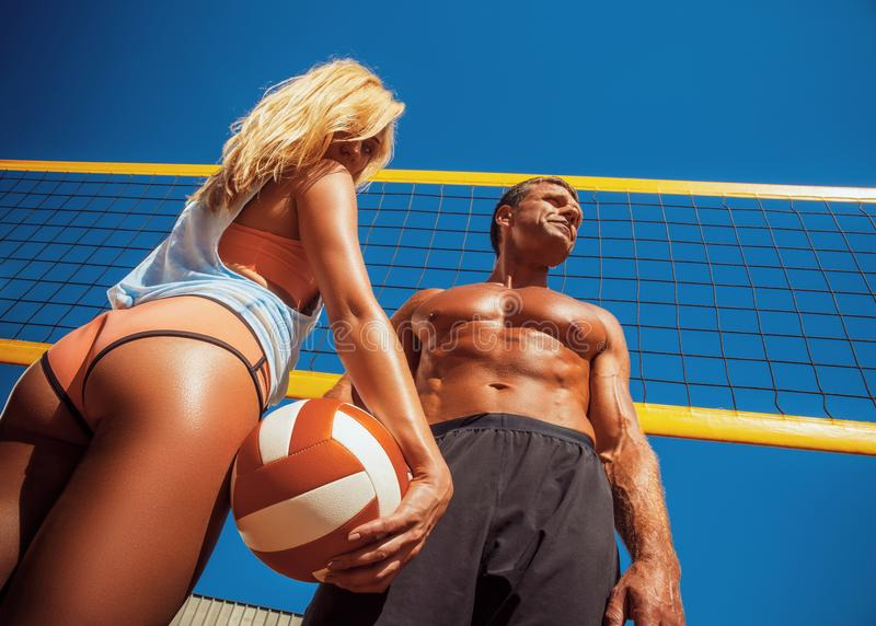 Sports couple. A handsome muscular tanned male and tanned blonde girl, standing on a volleyball ground. royalty free stock photography