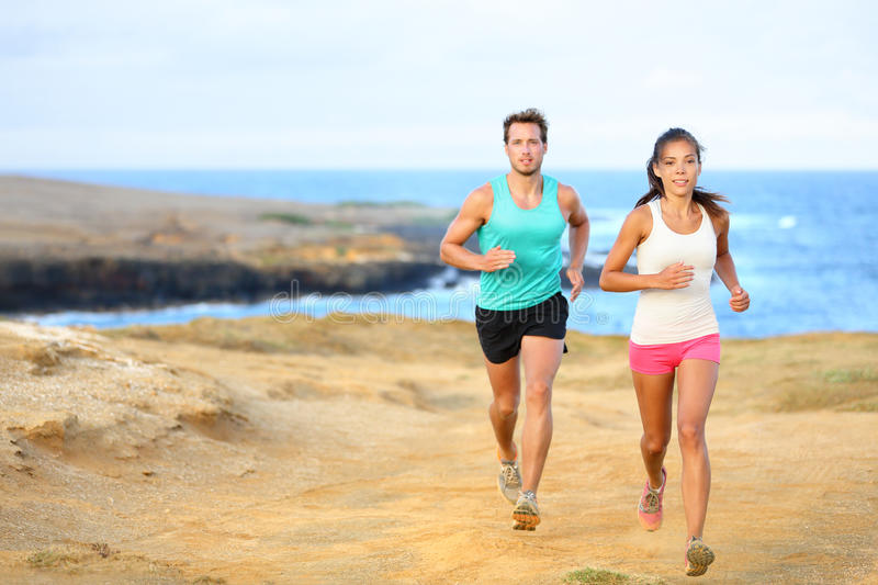 Sports couple jogging for fitness running outside. Sports couple jogging for fitness running in beautiful landscape nature outdoors. Young female and male sports stock photo