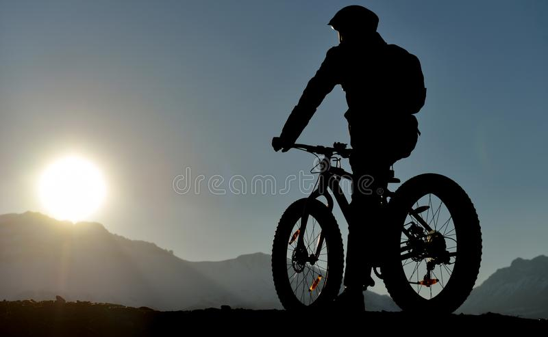 Sports cyclist silhouette. Silhouette of the back of a sports bicyclist sitting on his bike with one foot on the ground, facing toward the setting sun at the top stock images