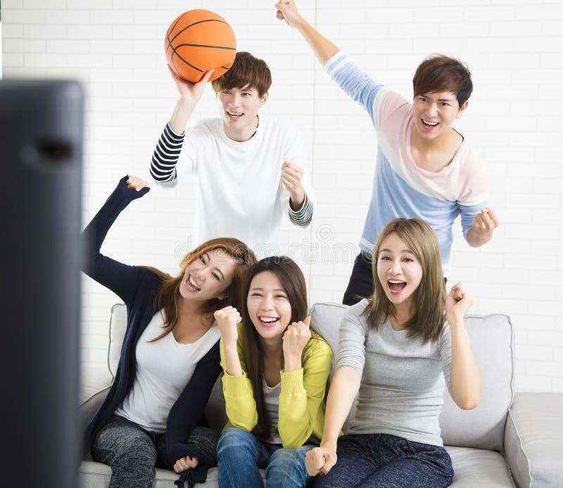 Sports de observation de jeune groupe à la télévision images stock